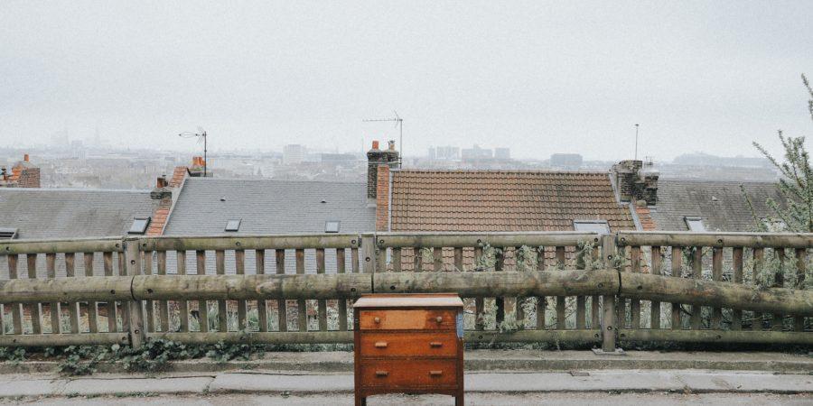 samotna komoda stojąca na placu w tle dachy domów