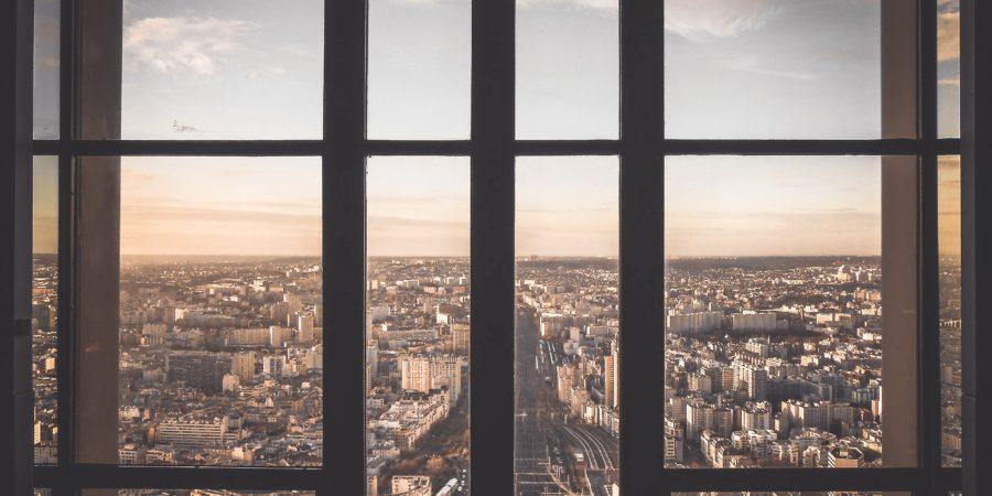 okno na świat za którym widać miasto o poranku